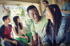 A group of friends, men and women at a house party drinking wine. Stock Photos