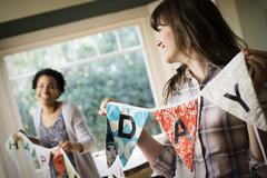 Two women hanging up bunting with lettering, decorating for a party. - stock photo