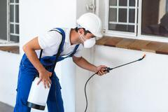 Pest worker spraying insecticide below window - stock photo