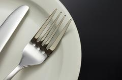 knife and fork at plate on black - stock photo