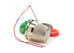 sewing thimble and thread with needle - stock photo