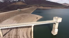 High aerial shot of low mountain reservoir and dam Stock Footage