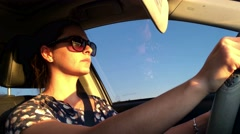 Drive. Decided thirty year old woman driving during sunset time Stock Footage