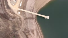 Very high rotating aerial of low mountain reservoir and dam Stock Footage