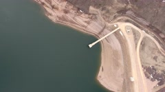 Very high rotating aerial shot of low mountain reservoir and dam Stock Footage