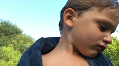 Child drying himself up after the pool. Expressive kid looking off camera Stock Footage
