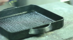 Chef pours olive oil on a grill pan Stock Footage