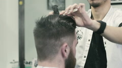 Hairdresser spraying water on the hair and combing hair - stock footage