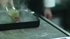 Chef turning  steaks on grill pan Stock Footage