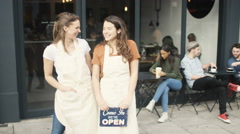 4K Happy women outside cafe hold up a sign to show they are open for business - stock footage