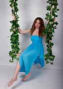 Beautiful young leggy redhaired woman in a long blue dress on a swing, wooden - stock photo