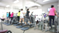 Blurred group of women and men doing sport on treadmill and bicycle - stock footage