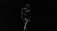 4K MMA fighter throwing kicks & punches in the fighting cage - stock footage