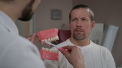 Dentist explains the man how to properly brush their teeth Stock Footage