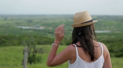 Girl looking at the countryside and adjusting hat.Woman adjusting her hat  Stock Footage