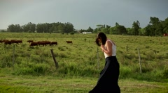 Girl in the countryside next to organic farming. Young woman walking in nature Stock Footage
