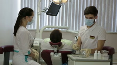Young dentist and his assistant treat teeth middle-aged man Stock Footage
