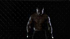 4K Muscular MMA fighter holding on to the fencing of the cage - stock footage