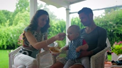 Parent feeding baby food. Medium shot of mom and dad in their late 30's feeding Stock Footage