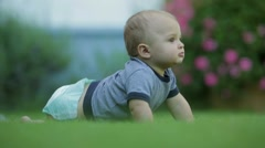 Baby learns to crawl while in outdoors. Toddler exploring the garden Stock Footage