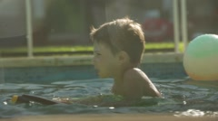 Young boy having fun by the pool during summer time holidays. Kid plays  Stock Footage