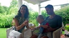 Parents feeding their one year old baby a healthy meal while in outdoor balcony Stock Footage