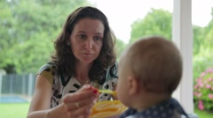 Mom feeding baby food to her infant month's old toddler. Stock Footage