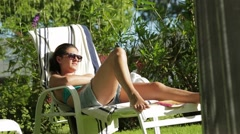 Girl sunbathing by the pool. Candid shot of young woman enjoying the sun Stock Footage