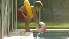 Kid having fun at the pool. Child walks by the poolside and grabs ball. Stock Footage