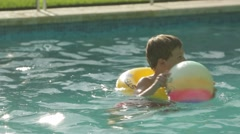 Kid inside the swimming pool with an inflatable ring and holding a ball Stock Footage