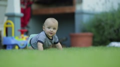 Baby in outdoor garden. Learning to crawl and to observe the world around him Stock Footage