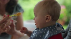 Happy baby being fed baby food while in outdoor balcony. Medium shot of infant Stock Footage