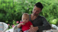 Baby in his father's lap with a garden background. Stock Footage