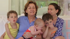 Mother, grandmother, kids, and baby posing for a family photo. Grandma, mom Stock Footage