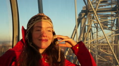 Beutiful young woman smiling and looking forward from height in the ferris wheel - stock footage
