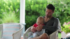 Father and baby : Infant month's old baby on his dad's lap in outdoor balcony Stock Footage