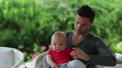 Dad holding his toddler one year old baby in his arms Stock Footage