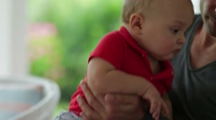 Father embracing his infant month's old baby in his arms : Dad bringing his new Stock Footage