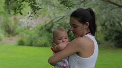 Young woman holding baby in outdoor garden.  Stock Footage