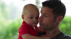 Candid spontaneous moment of a father kissing his infant son. Closeup of a dad Stock Footage