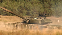 Big heavy tank driving through field with high grass at hot summer day Stock Footage