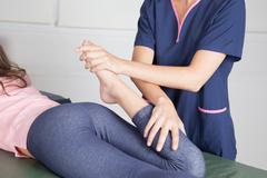 Physical Therapist  giving  a   leg treatment - stock photo