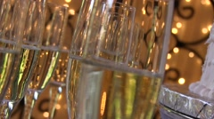 Pan past champagne glasses with bubbles and lights in the background Stock Footage