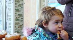 Little girl eating donat Stock Footage