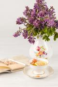 Tea with  lemon and bouquet of  lilac primroses on the table - stock photo
