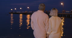 Senior couple in love by the sea at night - stock footage