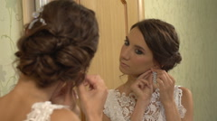 The bride wears an earring in the mirror Stock Footage