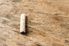 Cigarette butt discarded outdoors on the wooden table Stock Photos