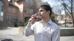 Young Man drinks red wine on the street of an old Europe town Stock Footage
