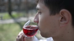Young Man drinks red wine on the street of an old Europe town - stock footage